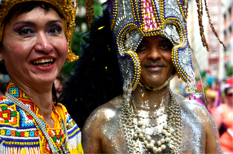 image of man and woman in brightly colored beaded costumes
