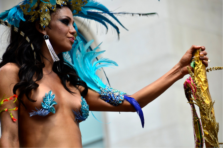 image of woman on parade float wearing blue feathered costume