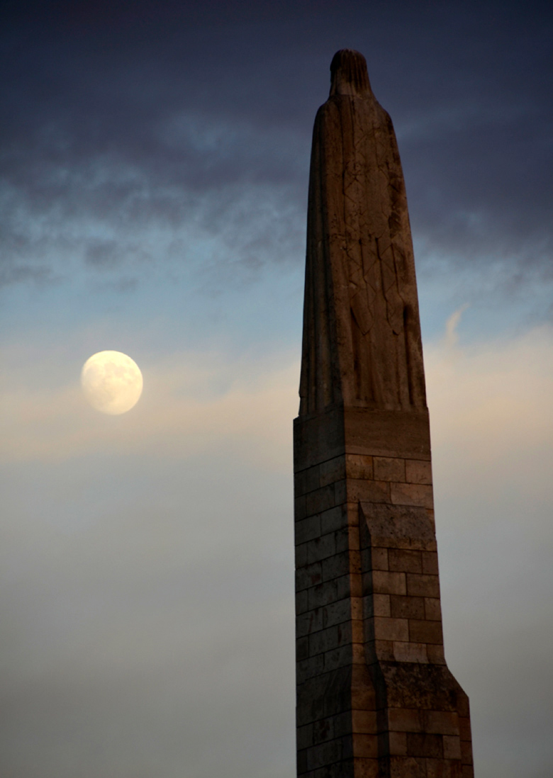 image of statue of Christ or a Saint watching a rising full moon