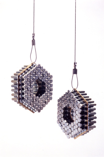 Nuts and bolts drilled into brass plate, hanging from wire